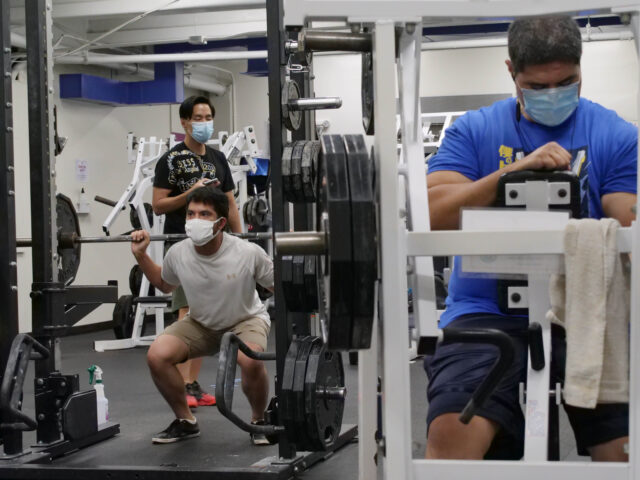 Rory Fraitaf (right) prepares to use a weight machine while others lift free weights behind him at the Nu'unau YMCA in Honolulu, HI, Thursday, July 30, 2020. Fraitaf says he comes to the gym everyday to exercise. (Ronen Zilberman photo Civil Beat)
