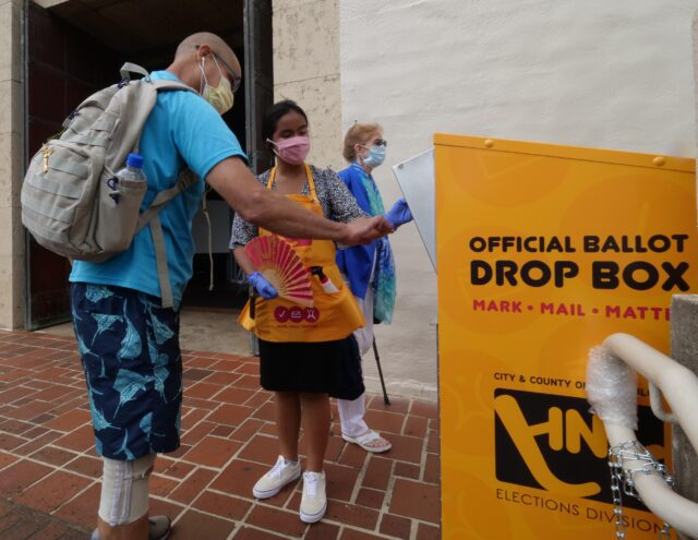 Kelly Dahling (center) a voter clerk, from the voter service center, opens the voting box so Honolulu resident Matthew Lindsey can cast his ballot at the Honolulu Hale, on Wednesday, August, 5, 2020. (Ronen Zilberman photo Civil Beat)