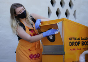 Voter Service Center worker Brooke Webb disinfects the official ballot collection box outside Honolulu Hale. August 6, 2020
