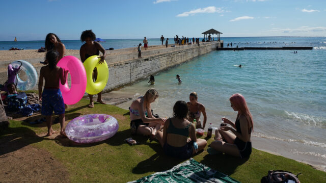 People gather near the Kapahulu Groin in Waikiki. Aug, 6 - Following a continued surge of COVID-19 cases and deaths, Mayor Caldwell's Emergency Order 2020-23 includes the closure of City parks, most park facilities, all campgrounds, Botanical Gardens, and Community Gardens from Saturday, August 8 through Friday, September 4, 2020.