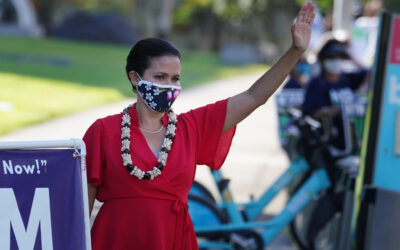 Honolulu Mayoral Candidate Kym Pine waves at passing motorists along Beretania Street near the Capitol.