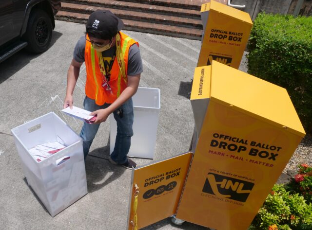 Levi Viloria a City & County of Honolulu election official empties a ballot collection box outside the Honolulu Hale in Honolulu, HI, Saturday, August 8, 2020. (Ronen Zilberman photo Civil Beat)
