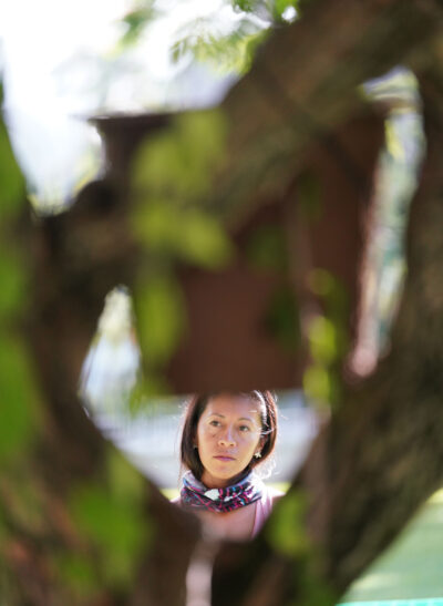 Beelieve owner Jasmine Joy checks out bee trap in a Bouganvillia bush near the rear of Iolani Palace.