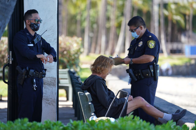 HPD officers hand out citations along Kalakaua avenue due to the Mayor's order that closed parks and beaches around Oahu due to COVID-19 pandemic. August 12, 2020