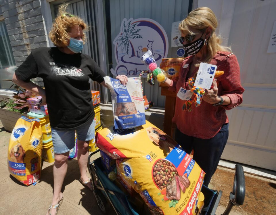 Kathy Ruper, Executive Director t of the Oahu SPCA, recieves a donation of pet food & supplies from Kina Knisley of Keller Williams on Friday, August 14, 2020. (Ronen Zilberman photo Civil Beat)