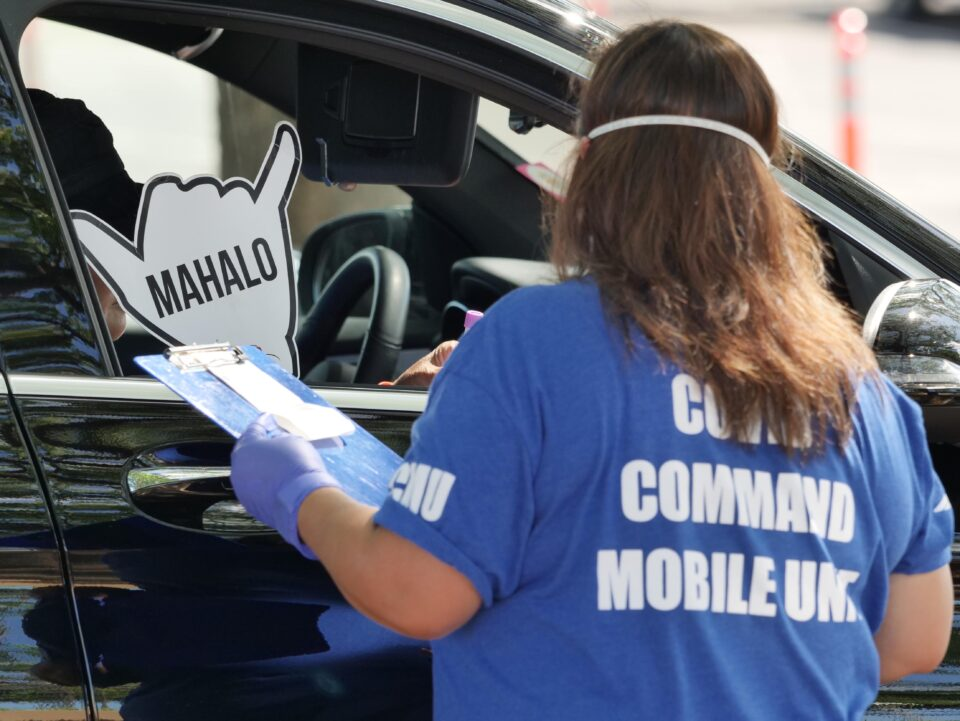 A member of the COVID Command Mobile Unit is greeted with a shaka by residents arriving for COVID-19 testing during a drive-thru event held in Kaka'ako Sunday, August 16, 2020. (Ronen Zilberman photo Civil Beat)