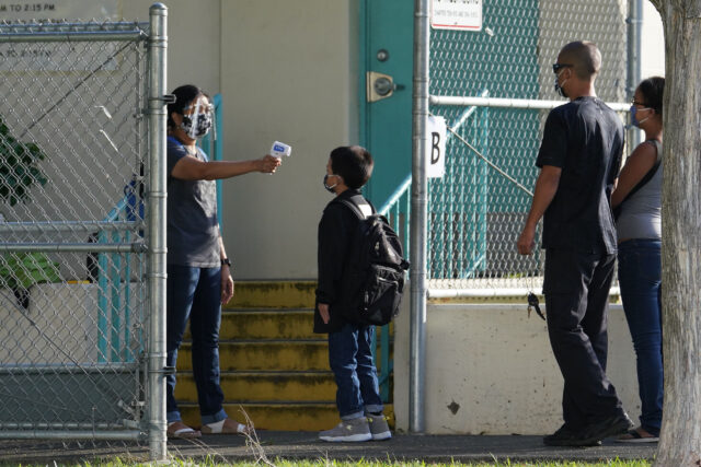 Kauluwela Elementary School staff uses a thermometer to check arriving students during COVID-19 pandemic. August 17, 2020