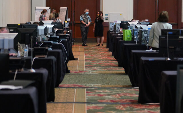 Emily Roberson, DOH Disease Investigation Branch Chief and Governor David Ige in a large room at the Hawaii Convention Center with banks of computers and contact tracing personnel. August 19, 2020