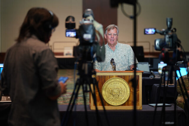 Department of Health Director Dr. Bruce Anderson speaks at podium with foreground, media cameras during contact tracing press conference held at the Hawaii Convention Center. August 19, 2020