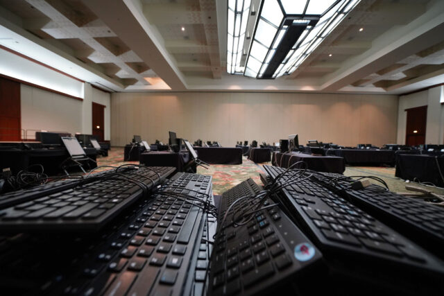 Pile of computer keyboards in an empty Hawaii Convention Center ballroom next to a operational Department of Health contact tracing ballroom with staff. Governor Ige earlier held a press conference in this room.
