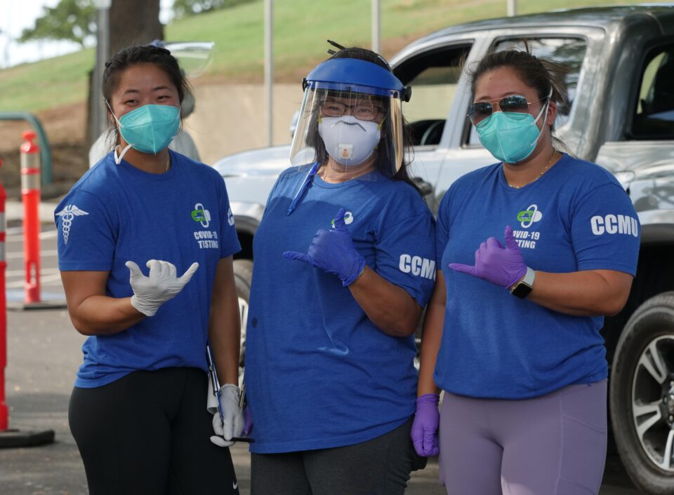 Celeste Horita (center) volunteers to help her daughters Chelsea Horita (left) and Cherise Horita (right) as they work with the COVID Command Mobile Unit during a drive-thru event held in Kaka'ako Sunday, August 23, 2020. (Ronen Zilberman photo Civil Beat)