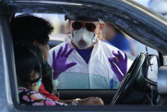 Premier Medical Group Hawaii team member esplain the swabbing process before performing a COVID-19 PCR swab test at Kakaako Waterfront Park parking lot. August 23, 2020