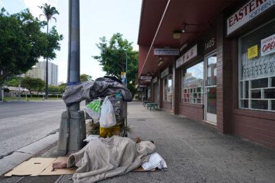 Houseless person sleeps on the sidewalk on King Street near Keeaumoku Street during COVID-19 pandemic. August 23, 2020