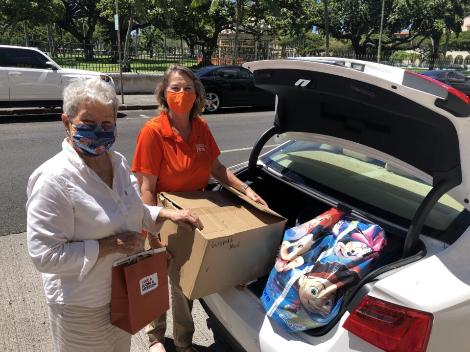 Dana Anderson of the Residential Youth Services and Empowerment picks up clothing donations provided by YWCA Oahu and YMCA of Honolulu. YWCA staffer Maryann Bray helps load the car.
