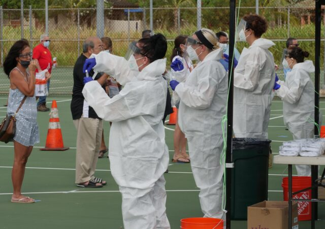 Medical technicians show people how to administer self-tests for COVID-19 during a free testing event at the Waimanalo District Park, Friday, August 28, 2020. (Ronen Zilberman photo Civil Beat)