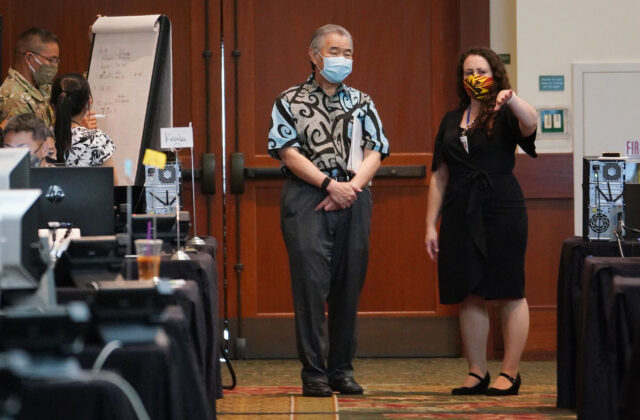 Departmentt of Health Investigations branch chief Emily Roberson talks with Governor Ige after press conference on August 19, 2020 at the contact tracing located in a ballroom at the Hawaii Convention Center.