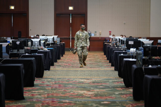 Hawaii Army National Guard member walks down newly place computer work stations on August 19, 2020 at the Hawaii Convention Center. August 19, 2020