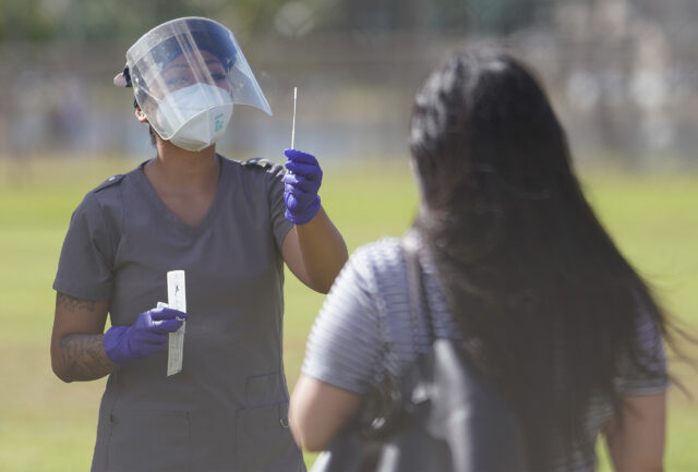 Medical personnel assist by giving directions on how to self swab during COVID-19 surge testing held at Ala Wai Park on the baseball field. September 5, 2020