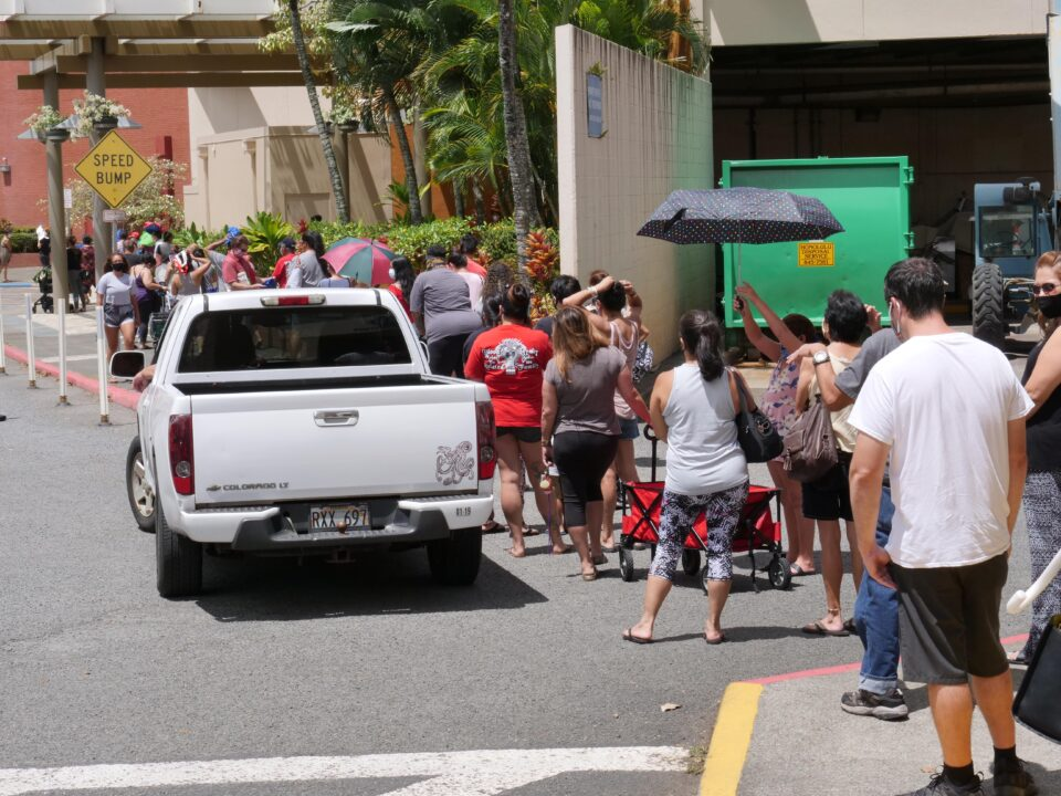 People lined up on foot and by cars to recieve free food at a distribution event put on by  the Hawai'i Health & Harm Reduction Center (H3RC) and the Hawai'i Foodbank, at the Windward mall in Kaneohe, HI, Tuesday, Sept. 8, 2020. (Ronen Zilberman photo Civil Beat)