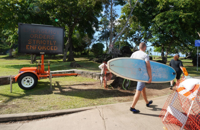 Beachgoer walks past Ala Moana Beach park sign 'Emergency Orders Strictly Enforced'. Today, Mayor Caldwell announced another 2 weeks of stay at home with opening beaches and parks with restrictions. September 8, 2020