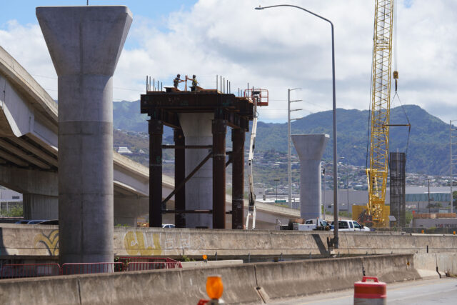 Silhouettes of workers high atop rail guideway columns near Middle Street/Keehi area as columns march towards the Honolulu city core. September 17, 2020