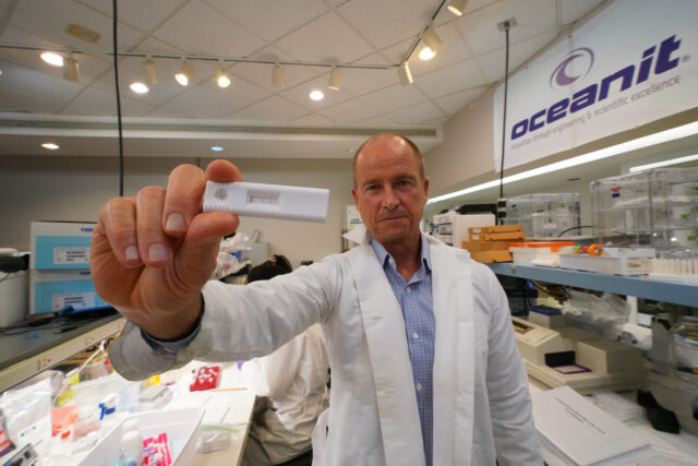 Oceanit Founder and CEO Patrick K Sullivan holds a Assure 19 test kit in the laboratory.