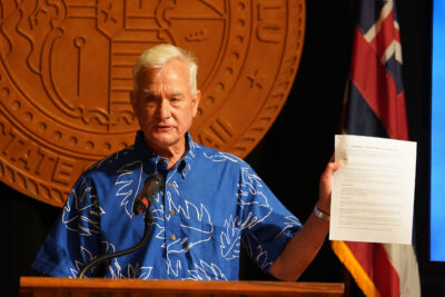 Mayor Kirk Caldwell holds some of the documents outlining the partial reopening of Honolulu on thursday.