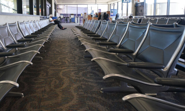 Lone passenger sits in an empty row of chairs at the Daniel K. Inouye International Airport interisland terminal during a COVID-19 pandemic. September 23, 2020