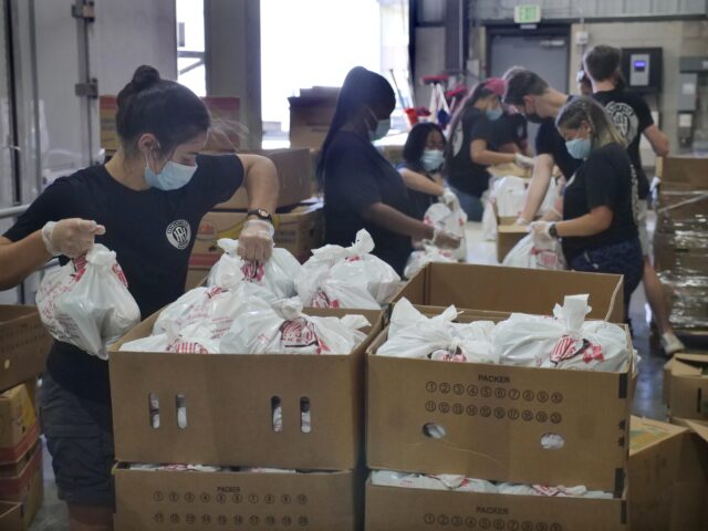 (left) Raven Svenson and other volunteers from the Revolution Hawaii group with the Salvation Army, prepare packages for a food drive at the Hawaii Food Bank in Honolulu in order to help families impacted by the COVID-19 pandemic, Monday, September 29, 2020. (Photo: Ronen Zilberman/Civil Beat)