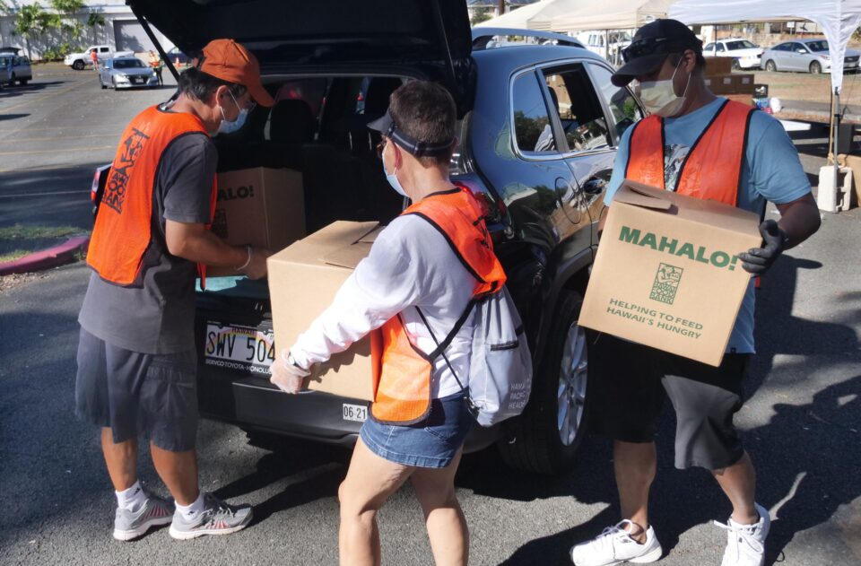 Volunteers from left to right: Won Oh, Judy Sakai, and Ramon Beatty load boxes of food into the trunks of waiting cars during a Kalihi pop-up food distribution put-on by the Hawai'i Foodbank at the Kalihi Valley District Park on Wednesday, Sept. 30, 2020. (Ronen Zilberman photo Civil Beat)