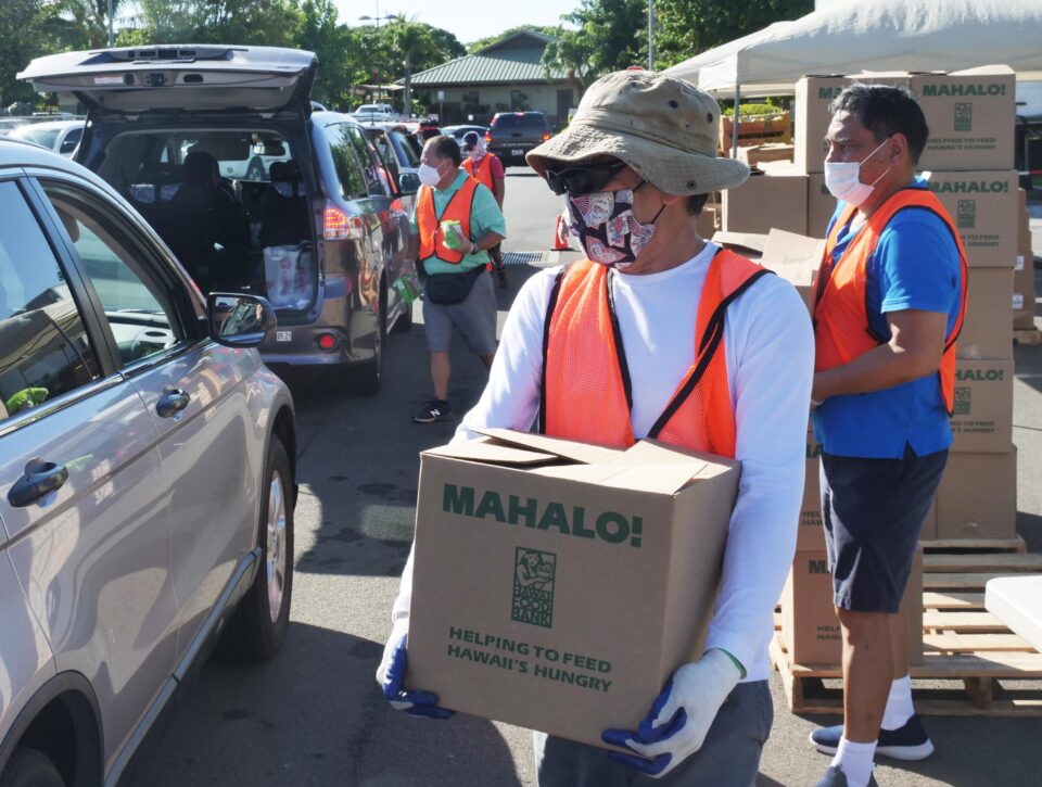 Mark Tachtay and other volunteers load boxes of food into the trunks of waiting cars during a pop-up food distribution event put-on by the Hawai'i Foodbank at the Ewa Pu'uloa District Park on Tuesday, Oct. 7, 2020. (Ronen Zilberman photo Civil Beat)