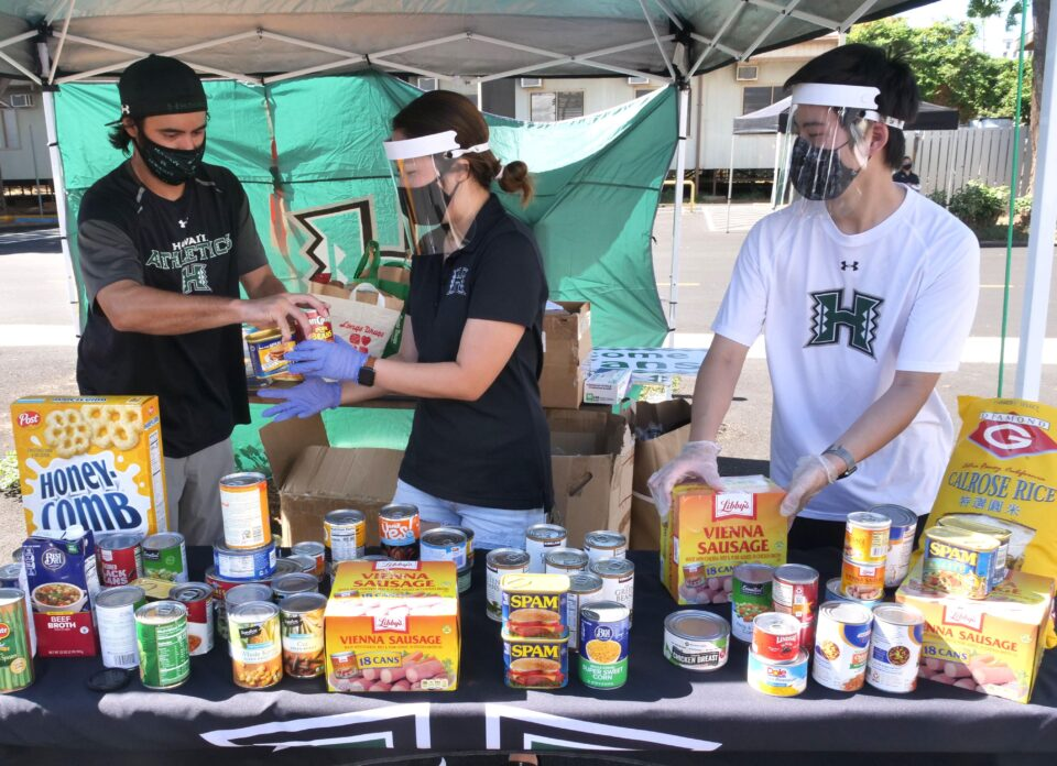 UH student volunteers from left, Cory Enriques, Jaymie Ho, and Justin Woo organize food donations dropped off by UH fans at the Stan Sheriff Center parking lot. Tuesday, Oct. 7, 2020. The food drive is part of the 'Bows Together initiative. (Ronen Zilberman photo Civil Beat)