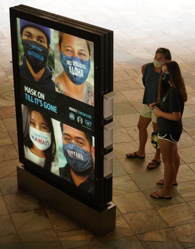 Shoppers stand near an advertisement at Ala Moana Center advocating for 'Mask On' during COVID-19 pandemic. October 12, 2020