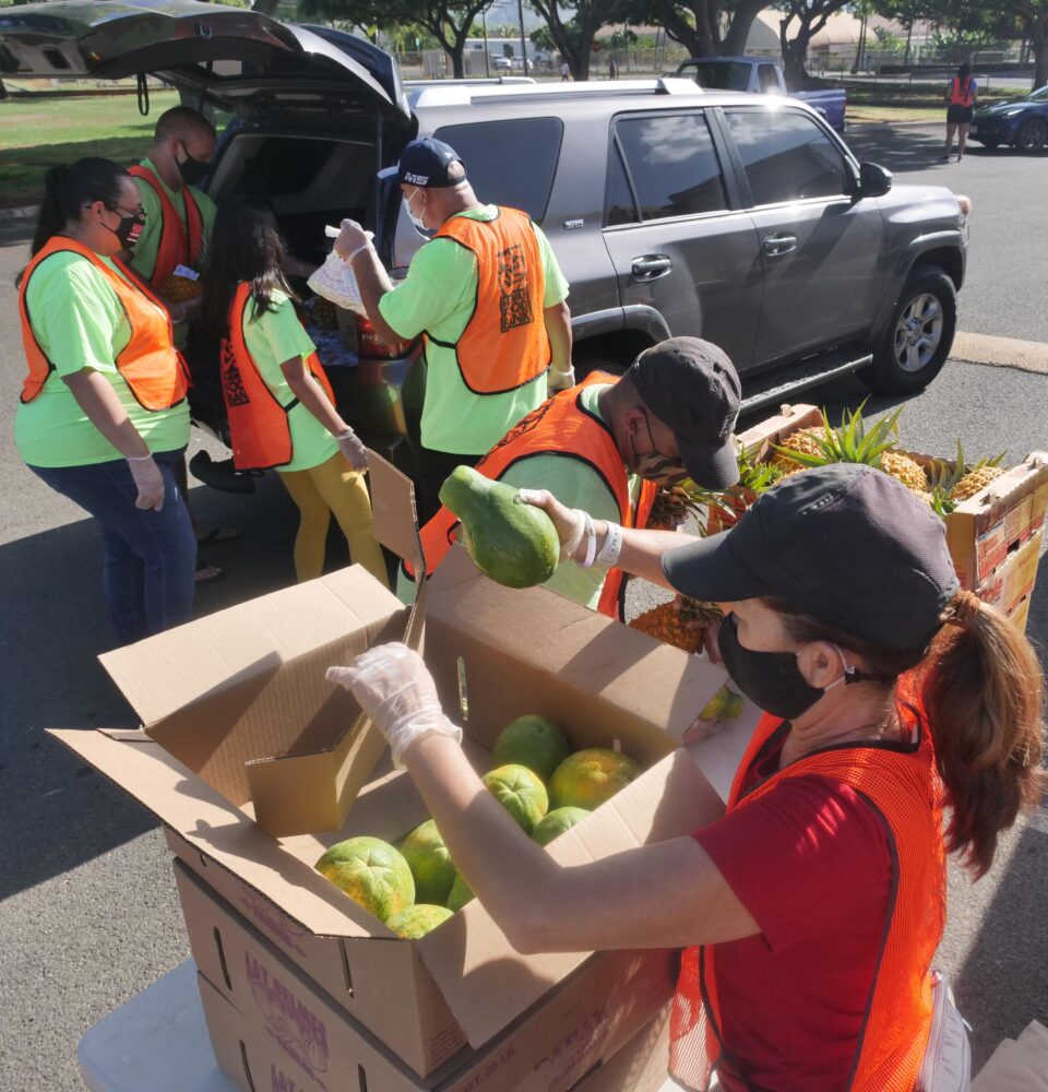 Volunteers load boxes of food into the trunks of waiting cars during a pop-up food distribution event put-on by the Hawai'i Foodbank at the Wai'anae District Park on Wednesday, Oct. 14, 2020. (Ronen Zilberman photo Civil Beat)