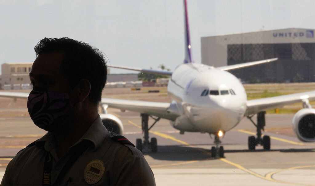 Silhouette of an airport security personnel as an arriving Hawaiian Airlines flight arrives at Daniel K. Inouye International Airport as transpacific travel is beginning to resume from today during COVID-19 pandemic. Passengers are required to have a COVID-19 test before arriving to Hawaii. October 15, 2020