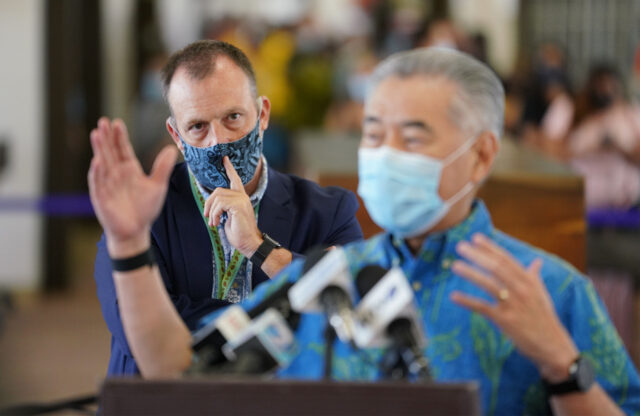 Lieutenant Governor Josh Green looks on with Governor David Ige in foreground, during the first day of lifting of a mandatory 14-day quarantine if arriving transpacific travelers received a negative COVID-19 test prior to arriving to Honolulu at Daniel K. Inouye International Airport during COVID-19 pandemic. October 15, 2020