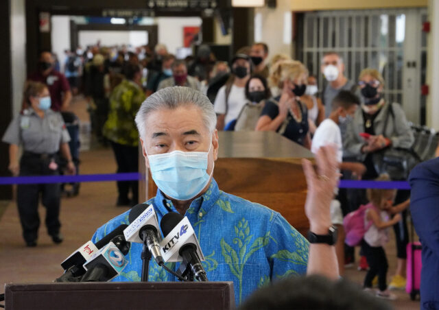 Hundreds of passengers arrive and wait in a slow moving line with Governor Ige in foreground during press conference. Arriving passengers are screened if they have pre-travel testing required to avoid the 14-day traveler quarantine. Tests are only accepted from trusted testing and travel partners. October 15, 2020