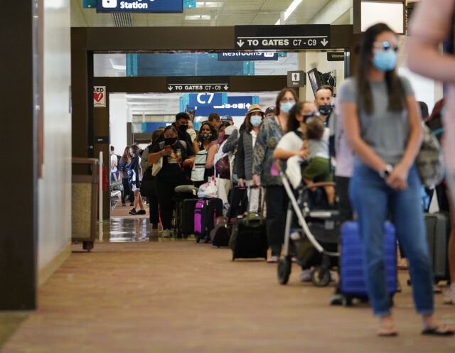 Hundreds of passengers arrive and wait in a slow moving line at Daniel K. Inouye International Airport. Arriving passengers are screened if they have pre-travel testing required to avoid the 14-day traveler quarantine. Tests are only accepted from trusted testing and travel partners. October 15, 2020