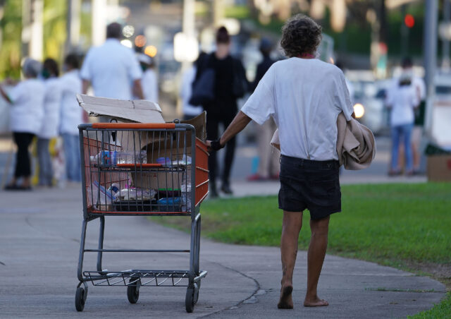 Person pushes their cart with their belongings barefooted fronting the Capitol during COVID-19 pandemic. October 14, 2020