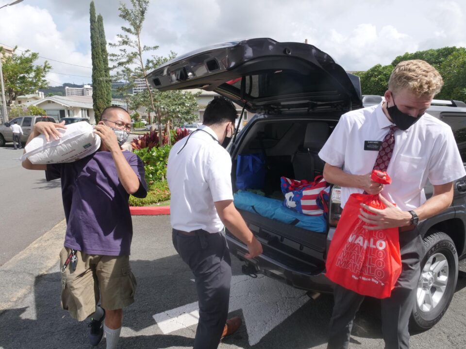 Volunteers (left) Franky Pudja, Elder Fajardo and Elder Higbee from The Church of Jesus Christ of Latter-day Saints unload food from a car during a food drive in Honolulu Saturday, Oct. 17, 2020. (Ronen Zilberman photo Civil Beat)