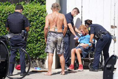 HPD officers assist a homeless man after he fell off his wheelchair near Kapahulu Avenue. October 19, 2020