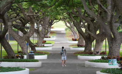 University of Hawaii at Manoa Mall usually is full with students changing classes and walking thru campus on a wednesday at midday. Lone masked student during COVID-19 pandemic. October 21, 2020