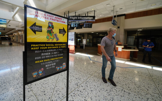 Daniel K. Inouye Airport signs warn to social distance and the wearing of masks during COVID-19 pandemic as Hawaii reopens to transpacific travelers on October 15, 2020