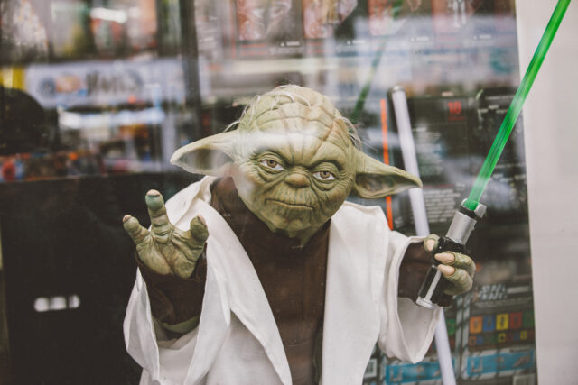 Paris, France - April 28, 2016: Portrait of Jedi Master Yoda toy model with green lightsaber on window display in Paris. Yoda is a fictional character in the Legend Star Wars Film franchise created by director George Lucas