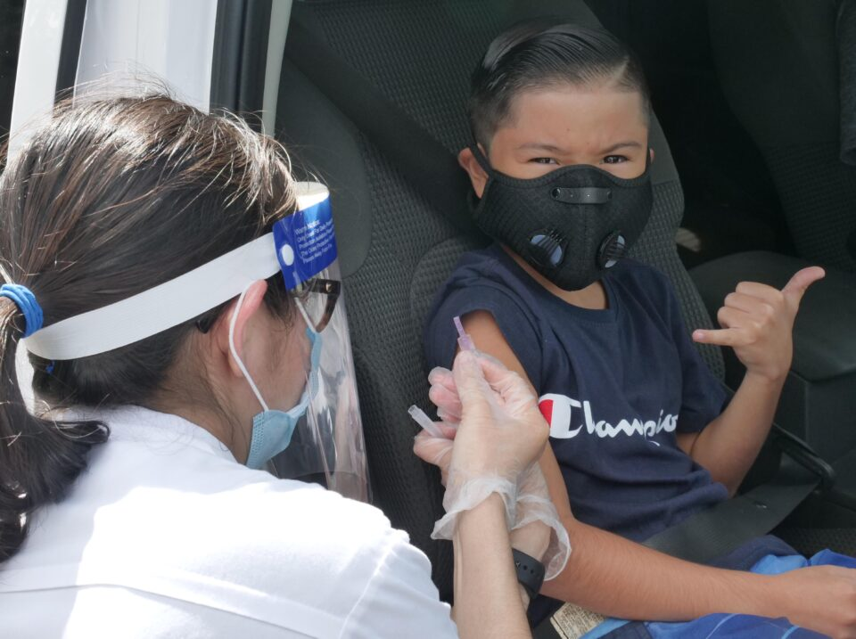 Melissa Machida administers a flu shot to 9-year-old Carter Santos, a Kaneohe resident, during a community drive-thru flu shot clinic at Windward Community College October 24, 2020. The event was sponsored by Hawaii Representatives Lisa Kitagawa and Scot Z. Matayoshi. (Ronen Zilberman photo Civil Beat)
