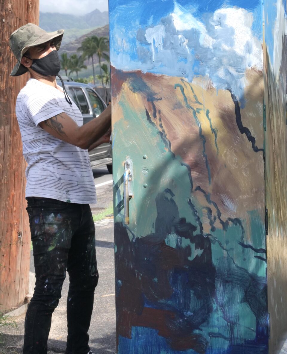 Waianae resident and artist Solomon Enos paints the surrounding mountains onto a traffic box on the Farrington Hwy in Waianae, HI, Saturday, October 24, 2020. The piece is part of a community project coordinated by Valley of Rainbows to beautify the 11.5-mile stretch of Farrington Highway in Leeward Oahu .  Artists will paint up to 25 traffic boxes with murals showcasing the beauty, legends, nature and stories of the Waianae Coast.