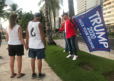 Unmasked Trump supporters hold flags along Kalakaua Avenue during COVID-19 pandemic. October 25, 2020
