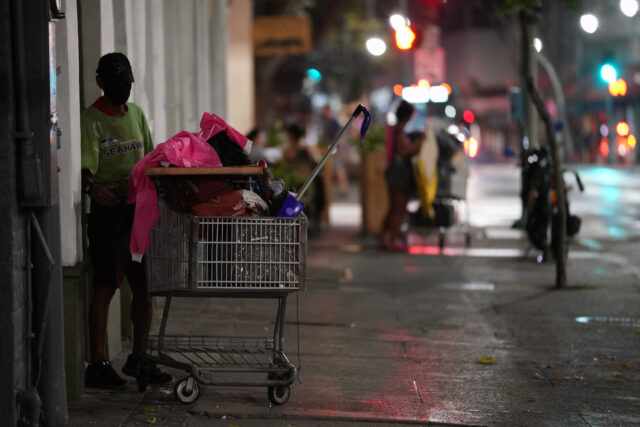 Masked person waits with his shopping cart along Hotel Street in Chinatown during COVID-19 pandemic. October 26, 2020