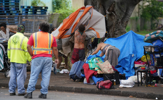 City and County workers stand by as a person throws their tent over the fence during a sweep along the sidewalks fronting Moiliili Neighborhood Park. October 27, 2020