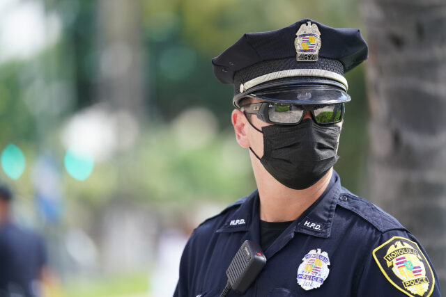 Masked HPD Honolulu Police officer patrols near the Waikiki substation. October 28, 2020